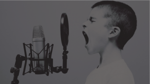 Menino praticando canto ou palestrando